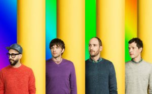The band OK Go stands between yellow poles.