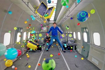 A man floats in air in a zero gravity plane, surrounded by colorful items.
